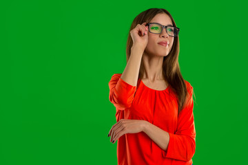 woman in glasses on green background looking away