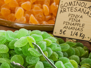 Traditional sweets (gominolas artesanas) made out of dried pineapple with sugar for sale on a market stand at Majorca,Spain, Europe -  no people, close-up