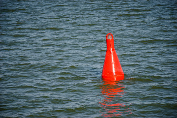 Floating red buoy on blue water