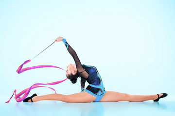 Photo sur Plexiglas Gymnastique The girl doing gymnastics dance with colored ribbon on a blue background