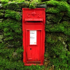 old-fashioned British mailbox postbox letterbox embedded in mossy wall