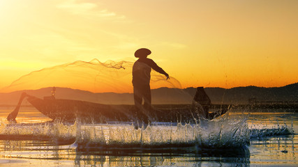 Silhouettes of the traditional stilt fishermen at sunrise in Thailand.