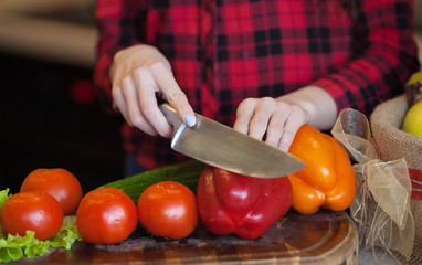 cooking and home concept - close up of female hand cutting vegetable on cutting board with sharp knife
