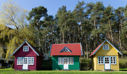 three multi-colored small house, tiny Homes on the lawn in the forest