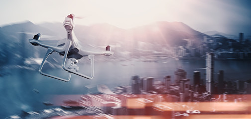 Photo White Matte Generic Design Remote Control Air Drone with action camera Flying Sky under City. Modern Megapolis Background. Wide, side view. Motion Blur,Flare Effect. 3D rendering.