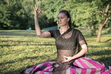 Pretty brunette woman wearing  indian dress in lotus pose