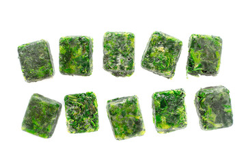 Cubes of frozen spinach on the white background