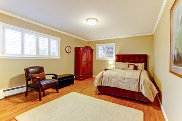 Guest bedroom with suede bed frame and hardwood floor.