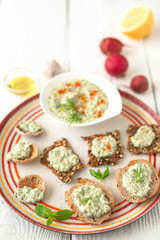 Colorful plate with different bread with tzatziki on the white table
