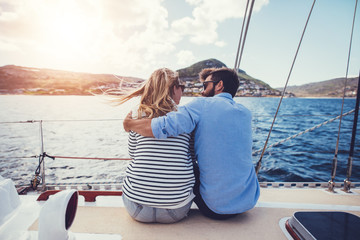 Rear view of young couple sitting on yacht deck