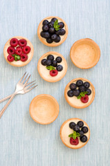 Delicious tartlets with raspberries and blueberries on blue background
