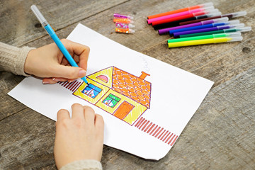 Close up of the hands of woman drawing a house with color pencil