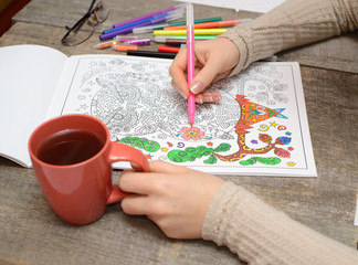 Woman coloring an adult coloring book and drinking tea, new stress reliving tool