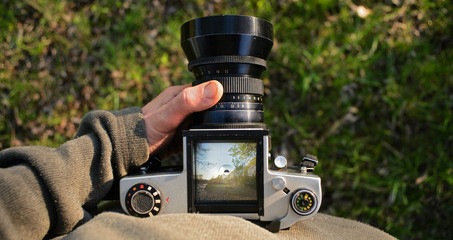 man photographer is making landscape photography with old film camera. top view