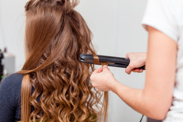 Stylist curling hair for brown haired woman. Girl care about her hairstyle