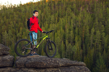 Cyclist on a cliff, the forest in the background