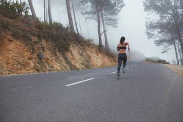 Female runner athlete sprinting on country road