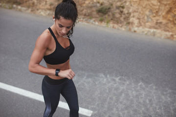 Fit young woman checking her progress on smart watch