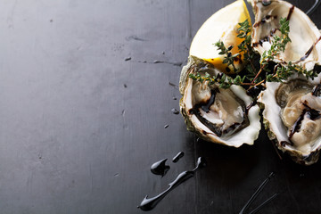 Fresh Oysters in shell with sauce and lemon