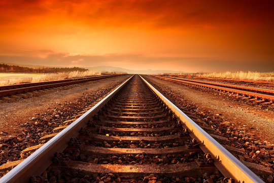 Train tracks goes to horizon in the majestic sunset.
