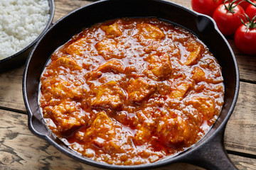 Butter chicken traditional Indian spicy curry meat food with rice in cast iron skillet on vintage wooden background. Karahi kadai chicken recipe.