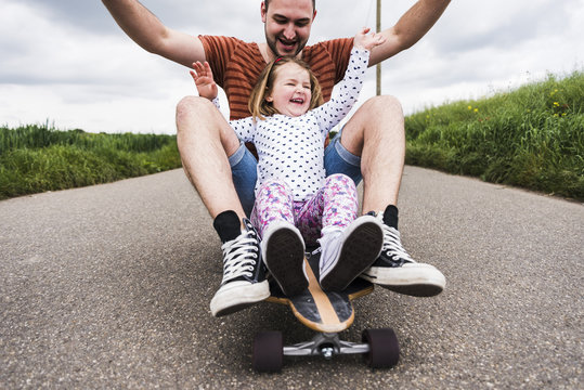 Daughter and father sitting on skateboard
