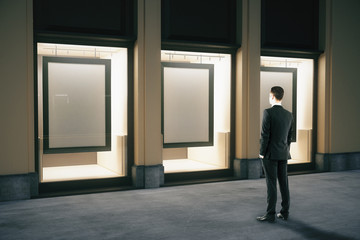 Showcase with frames and businessman