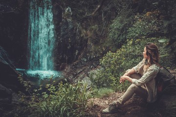 Beautiful woman hiker sitting near waterfall in deep forest.
