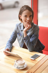 Young woman sitting in cafe with smartphone