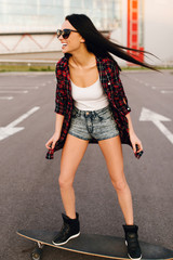 Hipster girl with skateboard. Lifestyle outdoor portrait