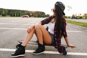 Beautiful and sexy girl sitting on the skateboard