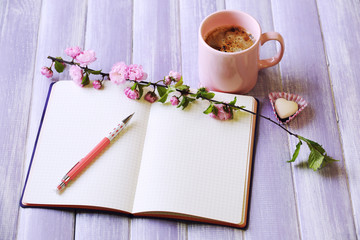Cup of fresh coffee and notebook on wooden background