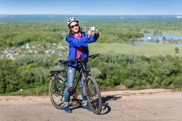 Beautiful woman cyclist take a self portrait with smart phone