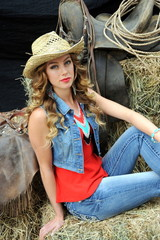 Cowgirl expressions inside a barn sitting on haystacks.