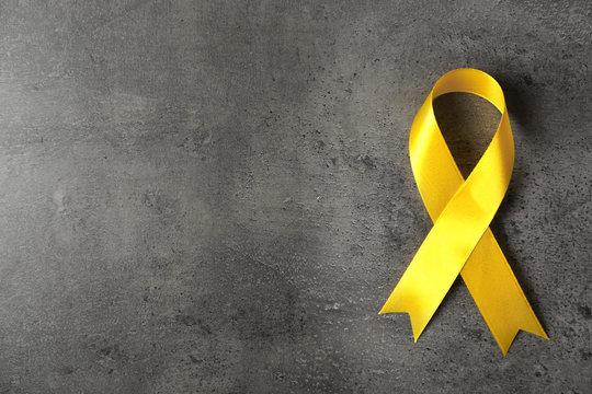 Yellow awareness ribbon on grey textured background
