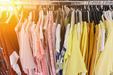 Choice of fashion clothes of different colors on metal hangers in cloth market