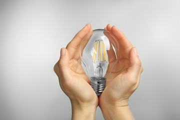 Woman hands holding bulb on grey background