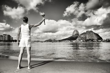 Athlete torchbearer standing with sport torch against the Rio de Janeiro Brazil skyline at Botafogo Beach with Guanabara Bay with Sugarloaf Mountain in monochrome
