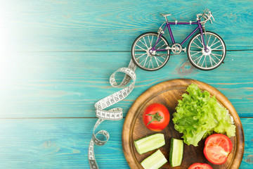bicycle model, fresh vegetables and centimeter tape on blue wood
