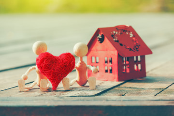 Two wooden little men with heart near house