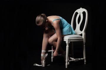 jeune fille 11 ans en tenue de danse classique mettant ses pointes sur chaise