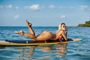 Sexy woman lying on a surfing board on the water