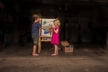 Boy painting girls face with paintbrush