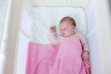 Sleeping newborn in travel crib