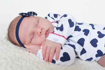 Fototapeta Cute newborn girl sleeps on fur plaid (3 weeks)