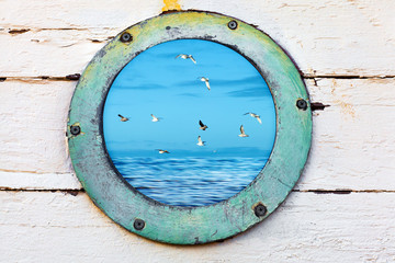 Vintage old porthole window looks out at birds and sea