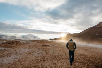 Rear view of man walking geothermal site