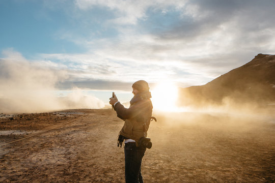side view of man on geothermal site using smartphone to take photograph
