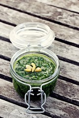 Homemade pesto with pine nuts on a rustic wooden table.Selective focus