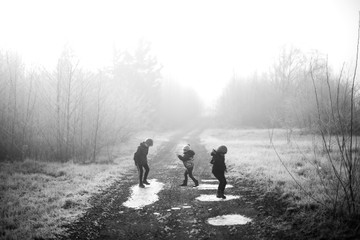 Three children playing on a path with frozen puddles - black and white